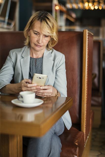 Woman on cellphone having coffee