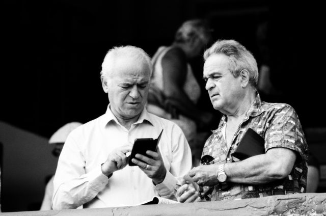 Older man using cell phone with another man